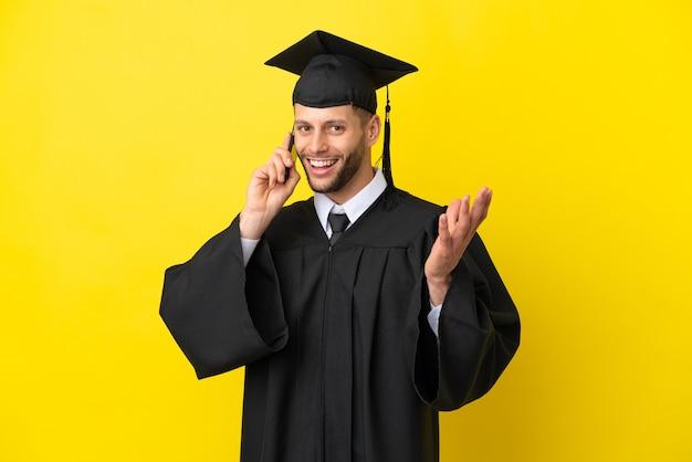 Jonge, universitair afgestudeerde blanke man geïsoleerd op een gele achtergrond die een gesprek voert met de mobiele telefoon met iemand