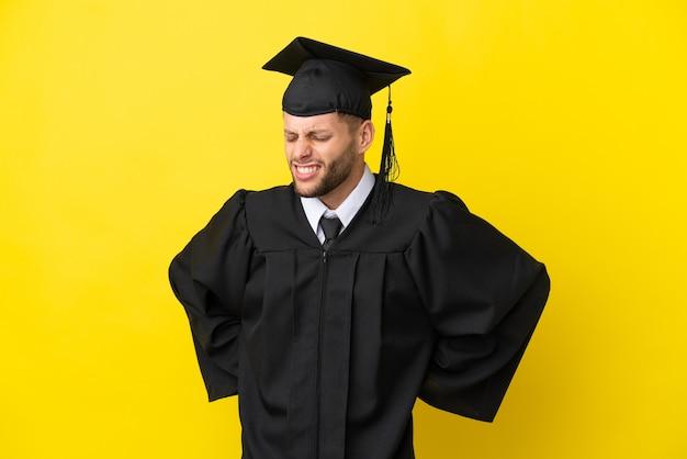 Jonge, universitair afgestudeerde blanke man geïsoleerd op een gele achtergrond die lijdt aan rugpijn omdat hij moeite heeft gedaan