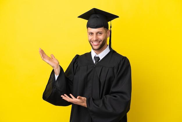 Jonge, universitair afgestudeerde blanke man geïsoleerd op een gele achtergrond die zijn handen naar de zijkant uitstrekt om uit te nodigen om te komen