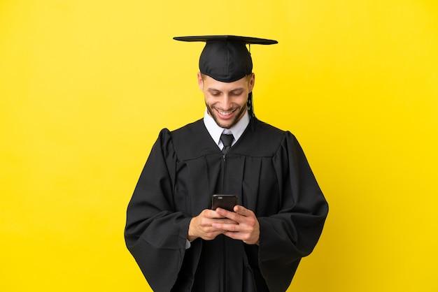 Jonge, universitair afgestudeerde blanke man geïsoleerd op gele achtergrond die een bericht verzendt met de mobiel