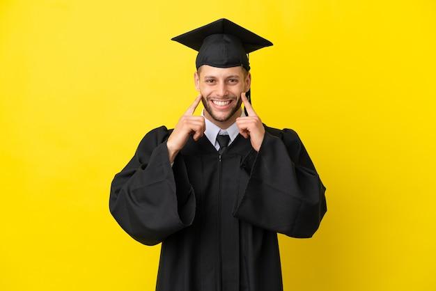 Jonge universitair afgestudeerde blanke man geïsoleerd op gele achtergrond glimlachend met een vrolijke en aangename uitdrukking