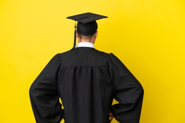Jonge universitair afgestudeerde blanke man geïsoleerd op gele achtergrond in achterpositie