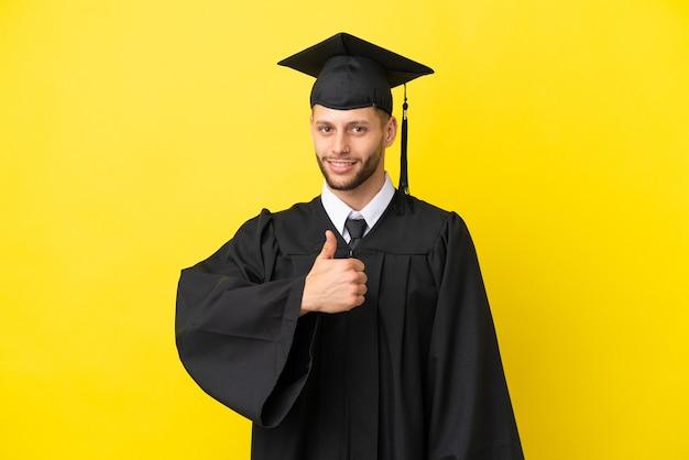 Jonge universitair afgestudeerde blanke man geïsoleerd op gele achtergrond met een duim omhoog gebaar