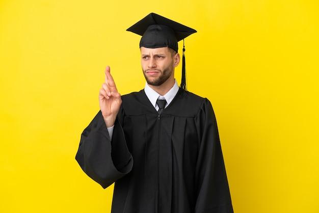 Jonge, universitair afgestudeerde blanke man geïsoleerd op gele achtergrond met vingers die elkaar kruisen en het beste wensen