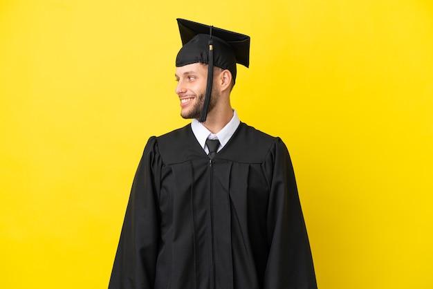 Jonge universitair afgestudeerde blanke man geïsoleerd op gele achtergrond op zoek naar kant