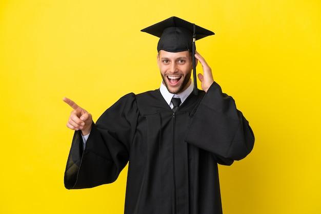 Jonge, universitair afgestudeerde blanke man geïsoleerd op gele achtergrond verrast en wijzende vinger naar de zijkant