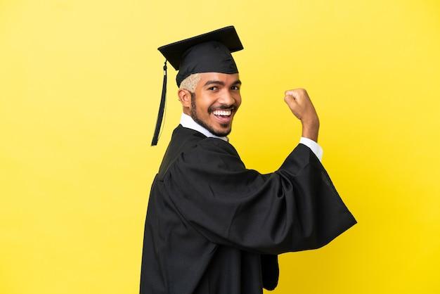 Jonge, universitair afgestudeerde colombiaanse man geïsoleerd op een gele achtergrond die een sterk gebaar doet