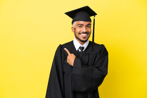 Jonge, universitair afgestudeerde colombiaanse man geïsoleerd op een gele achtergrond die naar de zijkant wijst om een product te presenteren