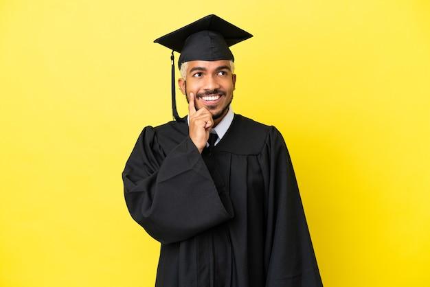 Jonge, universitair afgestudeerde colombiaanse man geïsoleerd op gele achtergrond die een idee denkt terwijl hij omhoog kijkt