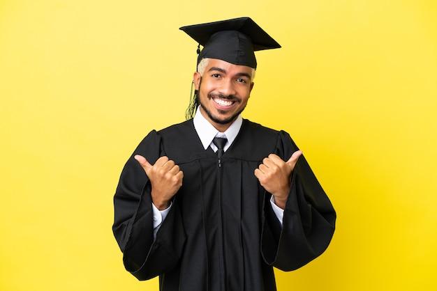 Jonge universitair afgestudeerde colombiaanse man geïsoleerd op gele achtergrond met duim omhoog gebaar en lachend
