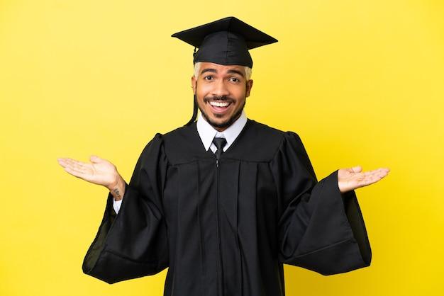 Jonge, universitair afgestudeerde colombiaanse man geïsoleerd op gele achtergrond met geschokte gezichtsuitdrukking