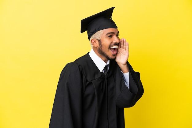 Jonge, universitair afgestudeerde colombiaanse man geïsoleerd op gele achtergrond schreeuwend met de mond wijd open naar de laterale