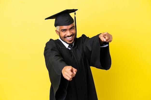 Jonge, universitair afgestudeerde colombiaanse man geïsoleerd op gele achtergrond wijst vinger naar je terwijl hij lacht