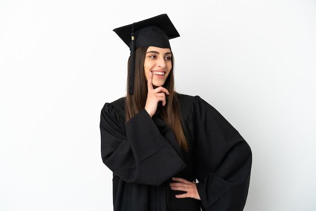 Jonge universitair afgestudeerde geïsoleerd op een witte achtergrond die een idee denkt terwijl hij omhoog kijkt