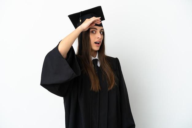 Jonge universitair afgestudeerde geïsoleerd op een witte achtergrond doet een verrassingsgebaar terwijl hij naar de zijkant kijkt