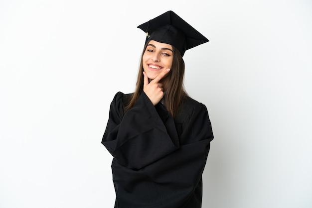 Jonge universitair afgestudeerde geïsoleerd op een witte achtergrond gelukkig en lachend