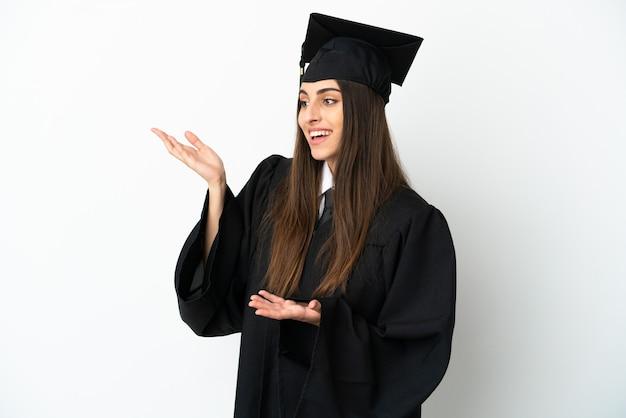 Jonge universitair afgestudeerde geïsoleerd op een witte achtergrond met verrassingsuitdrukking terwijl hij opzij kijkt