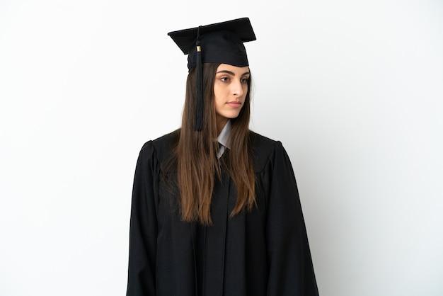 Jonge universitair afgestudeerde geïsoleerd op een witte achtergrond op zoek naar de kant