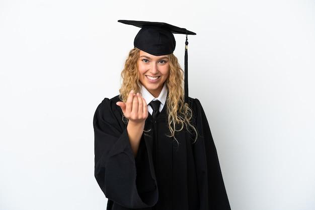 Jonge universitair afgestudeerde geïsoleerd op een witte achtergrond uitnodigend om met de hand te komen. blij dat je gekomen bent