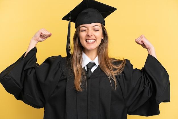 Jonge universitair afgestudeerde geïsoleerd op gele achtergrond doet sterk gebaar