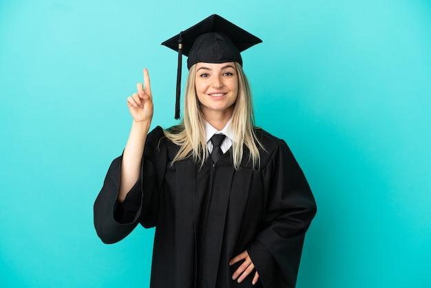 Jonge universitair afgestudeerde over geïsoleerde blauwe achtergrond die een geweldig idee benadrukt