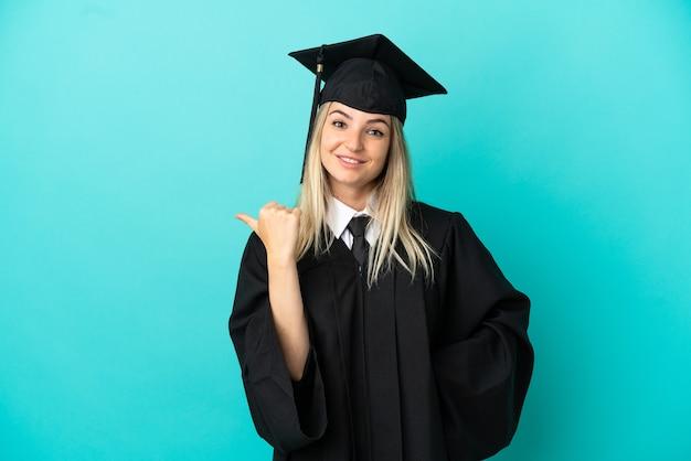 Jonge universitair afgestudeerde over geïsoleerde blauwe achtergrond die naar de zijkant wijst om een product te presenteren