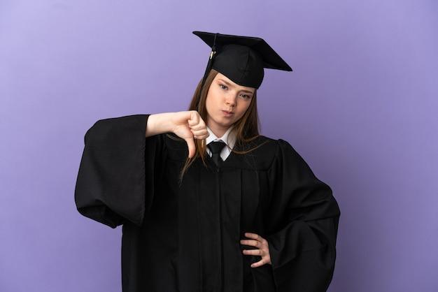Jonge universitair afgestudeerde over geïsoleerde paarse achtergrond met duim omlaag met negatieve uitdrukking