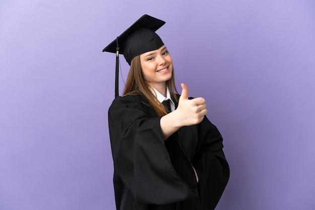 Jonge universitair afgestudeerde over geïsoleerde paarse achtergrond met duimen omhoog omdat er iets goeds is gebeurd