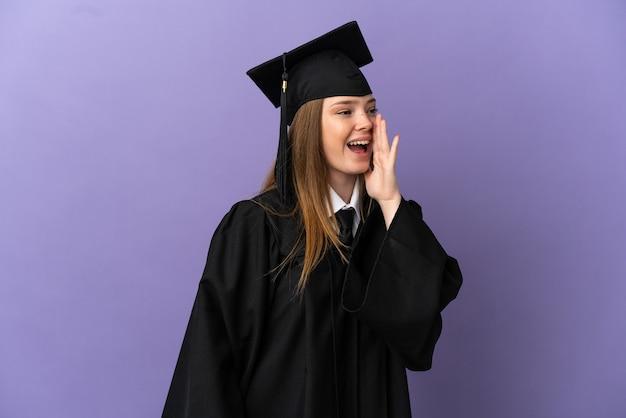 Jonge universitair afgestudeerde over geïsoleerde paarse achtergrond schreeuwend met de mond wijd open naar de zijkant
