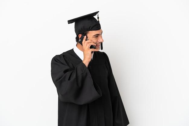 Jonge universitair afgestudeerde over geïsoleerde witte achtergrond die een gesprek voert met de mobiele telefoon met iemand