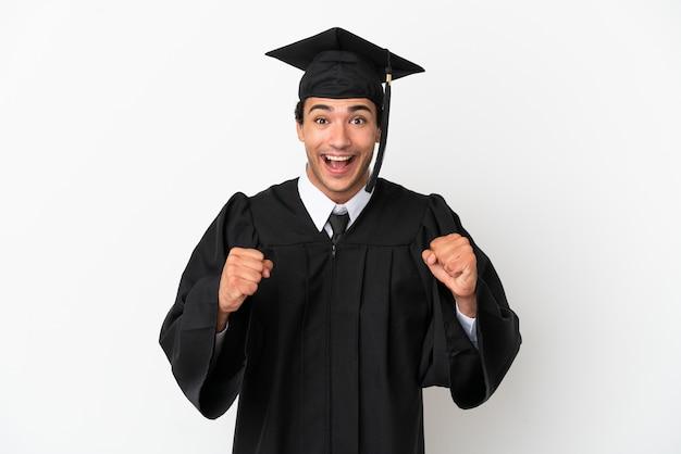 Jonge universitair afgestudeerde over geïsoleerde witte achtergrond die een overwinning viert in winnaarspositie