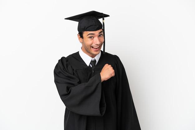 Jonge universitair afgestudeerde over geïsoleerde witte achtergrond die een overwinning viert