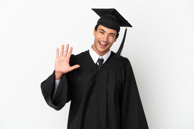 Jonge universitair afgestudeerde over geïsoleerde witte achtergrond die met de hand salueert met een gelukkige uitdrukking