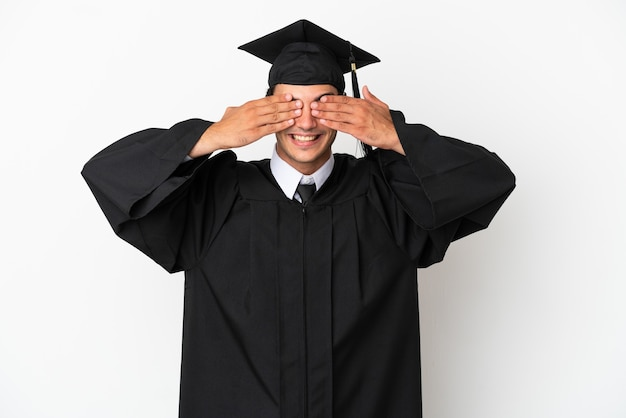 Jonge universitair afgestudeerde over geïsoleerde witte achtergrond die ogen bedekt door handen
