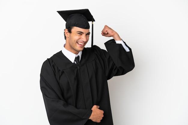 Jonge universitair afgestudeerde over geïsoleerde witte achtergrond doet sterk gebaar