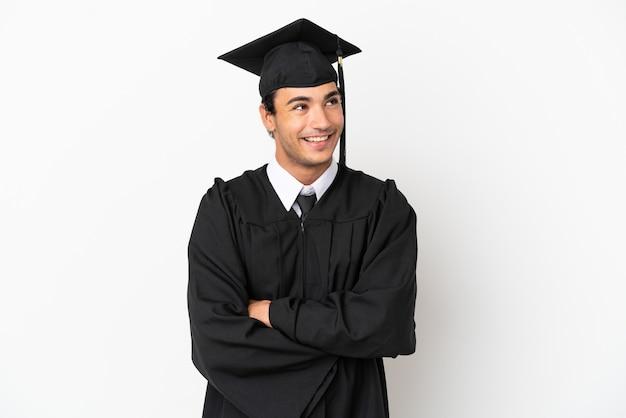 Jonge universitair afgestudeerde over geïsoleerde witte achtergrond gelukkig en glimlachend