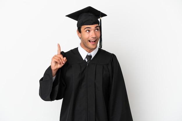Jonge universitair afgestudeerde over geïsoleerde witte achtergrond met de bedoeling de oplossing te realiseren terwijl hij een vinger opsteekt