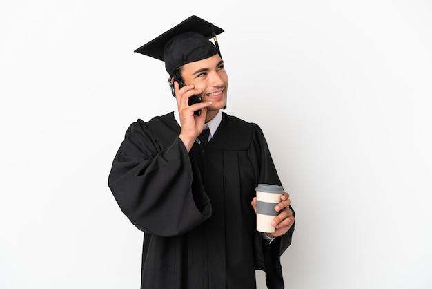 Jonge universitair afgestudeerde over geïsoleerde witte achtergrond met koffie om mee te nemen en een mobiel