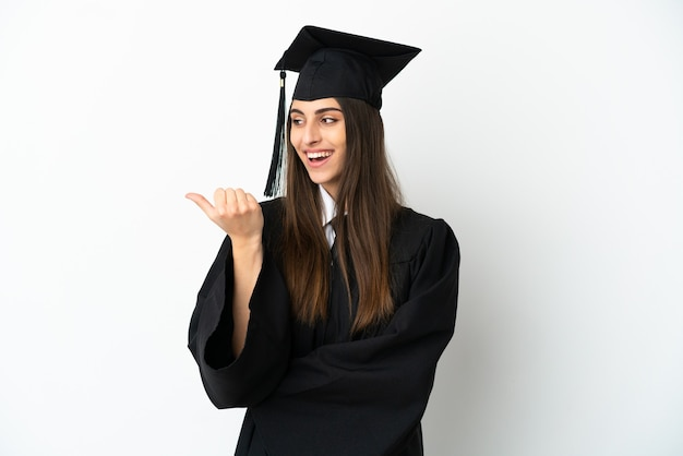 Jonge universitair afgestudeerde over geïsoleerde witte achtergrond wijzend naar de zijkant om een product te presenteren