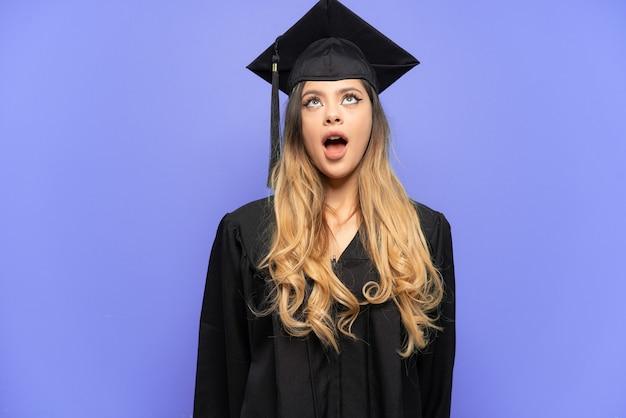 Jonge universitair afgestudeerde russisch meisje geïsoleerd op een witte achtergrond opzoeken en met verbaasde expression Premium Foto