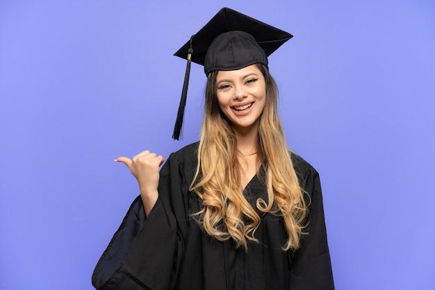 Jonge universitair afgestudeerde russisch meisje geïsoleerd op een witte achtergrond wijzend naar de zijkant om een product te presenteren
