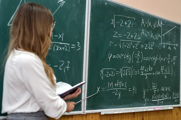 Jonge universiteitsleraar die wiskundige oefening op het bord schrijft tijdens een les. onderwijs