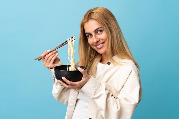 Jonge uruguayaanse blonde vrouw die over blauwe muur een kom noedels met eetstokjes houdt