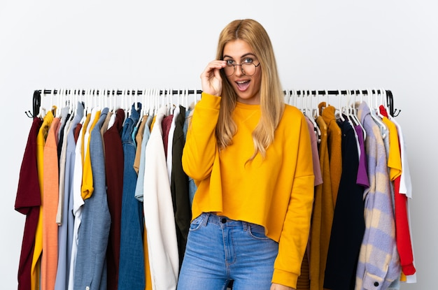 Jonge uruguayaanse blonde vrouw in een kledingwinkel met een bril en verrast