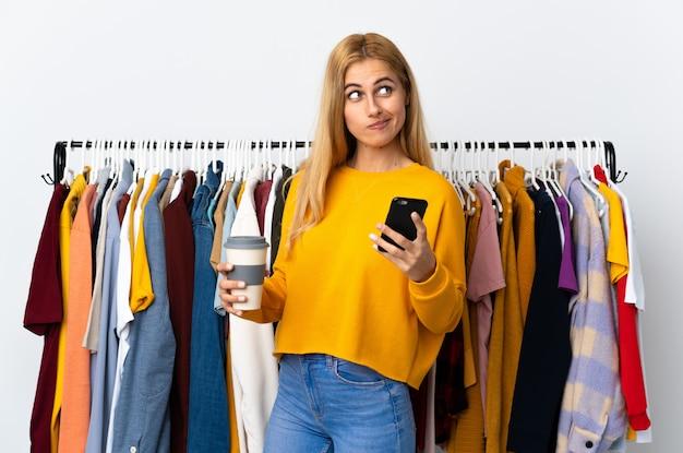 Jonge uruguayaanse blonde vrouw in een kledingwinkel met koffie om mee te nemen en mobiel terwijl ze iets denken