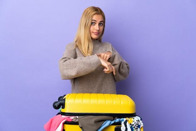 Jonge uruguayaanse blonde vrouw met een koffer vol kleren over geïsoleerde paarse muur die het gebaar maakt te laat te zijn