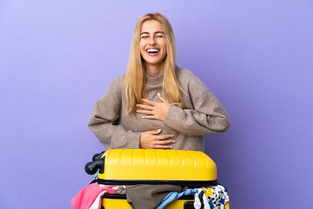 Jonge uruguayaanse blonde vrouw met een koffer vol kleren over geïsoleerde paarse muur lacht veel