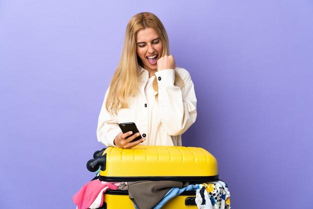 Jonge uruguayaanse blonde vrouw met een koffer vol kleren over geïsoleerde paarse muur met telefoon in overwinningspositie