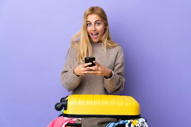 Jonge uruguayaanse blonde vrouw met een koffer vol kleren over geïsoleerde paarse muur verrast en het verzenden van een bericht
