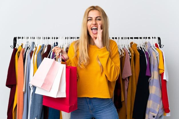 Jonge uruguayaanse blondevrouw in een kledingsopslag en het houden van het winkelen zakken die met wijd open mond schreeuwen